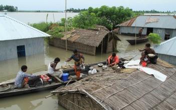 バングラデシュで屋根の上に避難する人や小舟の上で煮炊きをする人々