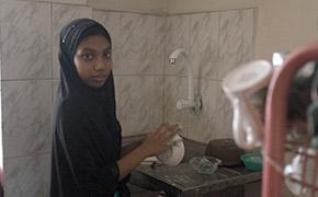 雇い主の家で洗い物をする家事使用人の少女
