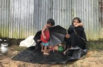 すわりこみぼーっとしている母親、子どもは濡れたビニールシートの上で寝ている(写真はジュマ・ネット提供)