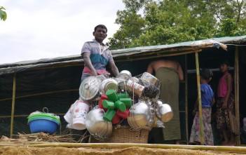 鍋や水かめ、ざるなどの生活用品を売り歩く男性。バングラデシュの農村ではよく見かける