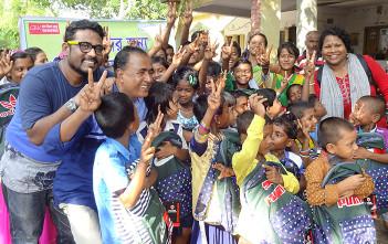 学用品を手にした子供たちと現地で活動したシャプラニールダッカ事務所職員のアニス(写真左)(シャンカルプール・ユニオンにて撮影)