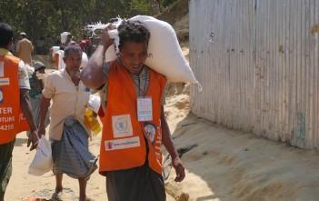 運搬作業を行うボランティア 少なくとも40キロ以上となる荷物を担ぐ重労働です