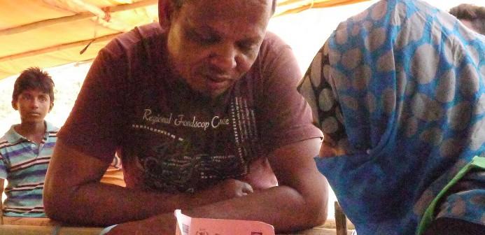 食料配布カード作成に訪れた男性の相談を受けるボランティア