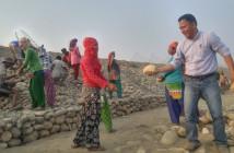 作業員と共に籠に石を詰める事業スタッフ_small