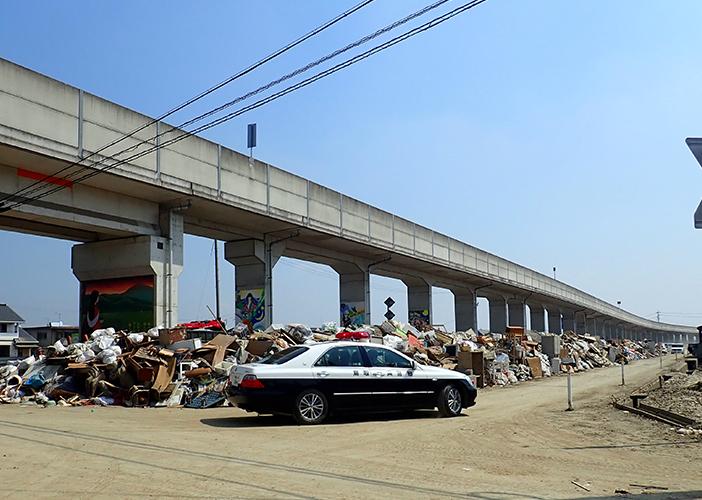 道路脇には家庭から出たゴミが積み上げられている。(2018年7月16日撮影)