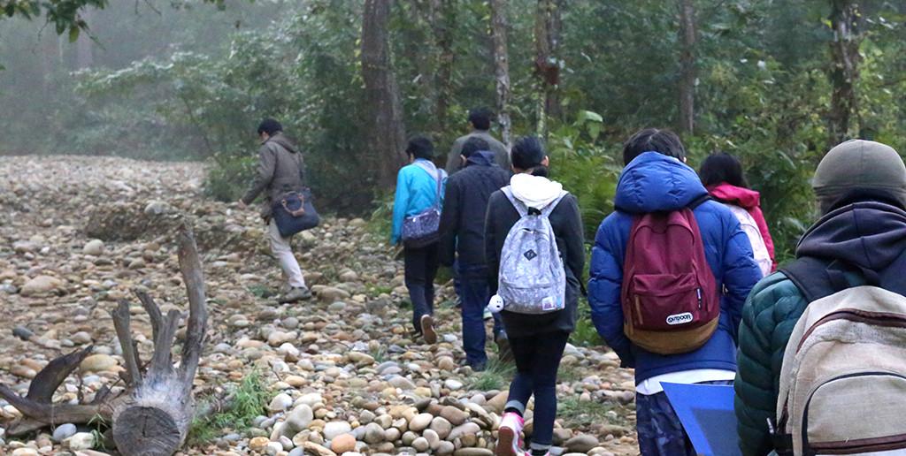 上流に向かって歩くツアー参加者。壊れた簡易ダムが放置されており、洪水時の水の威力が垣間見えた。