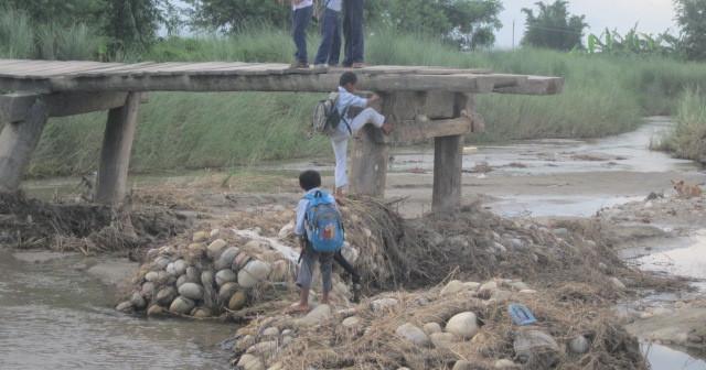 鉄砲水で損壊した橋と通学する子どもたち。