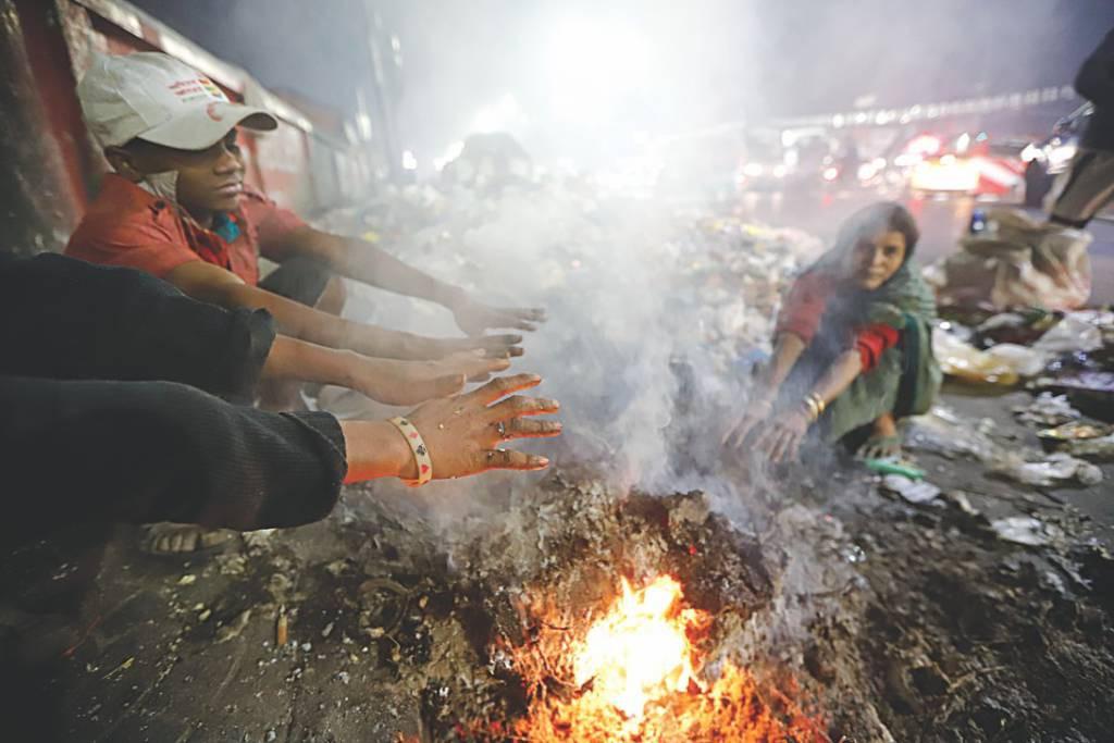 焚火で暖をとる人たち(Daily Starから写真を拝借)
