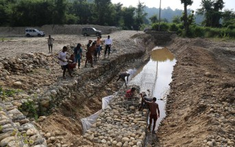 蛇篭(じゃかご:ワイヤーを籠状に成型し中に石をつめる)を利用し急流を緩めたりや上流から流れてくる土砂などをせき止める等の役割を果たしている。住民が作業している様子。